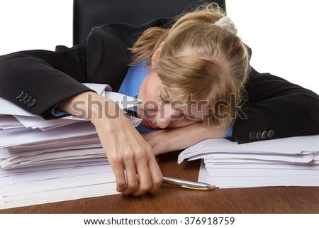Exhausted business woman has fallen asleep on the desk behind some piles of paperwork