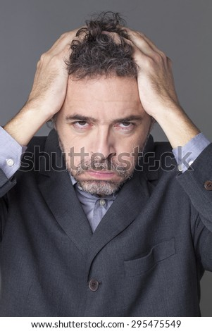 exhausted businessman holding his head with both hands expressing dramatic mistake at work - stock photo