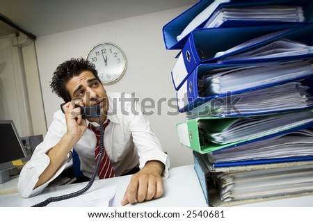 exhausted businessman in his office surrounded by files - stock photo