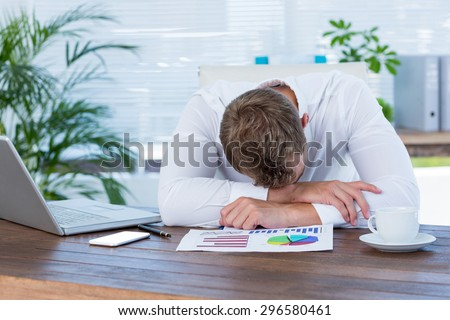 Exhausted businessman sleeping on the desk in the office - stock photo
