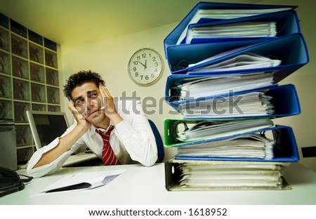 exhausted businessman surrounded by files - stock photo