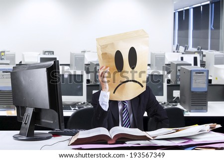 Exhausted businessman with cardboard head working in office - stock photo