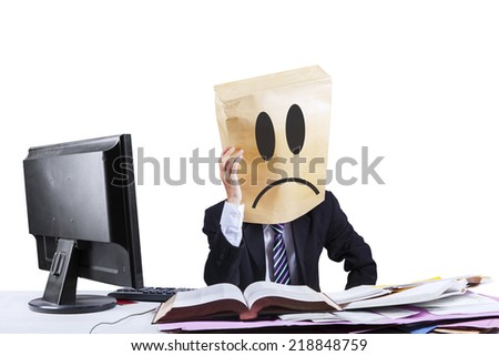 Exhausted businessman with cardboard head working in office. Isolated on white background - stock photo