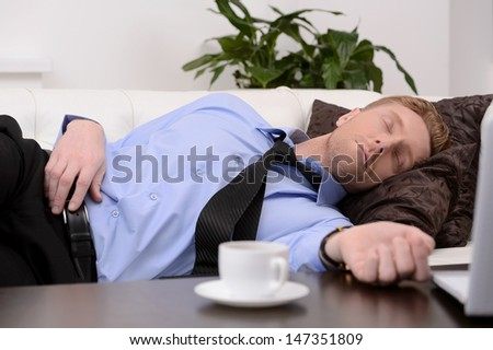 Exhausted businessman. Young tired businessman in formalwear sleeping on the couch - stock photo
