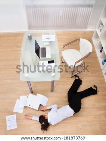 Exhausted Businesswoman Fainted On Floor At Workplace - stock photo
