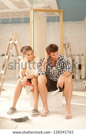 Exhausted couple sitting in bad mood in house under construction. - stock photo