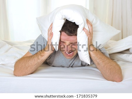 exhausted desperate young Man suffering hangover and headache with pillow on his head - stock photo