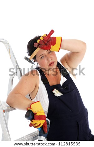 Exhausted DIY housewife or artisan Exhausted DIY housewife or artisan wearing dungarees and safety gloves leaning against her ladder with a tired expression clutching her tools - stock photo
