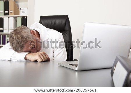 Exhausted doctor sleeping on his desk as he grabs a quick nap during his lunch break with his head resting on his arm on the desk - stock photo