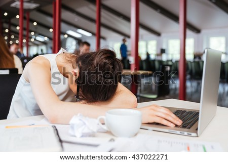 Exhausted fatigued young business woman sleeping on table with laptop at workplace - stock photo