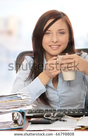Exhausted female relaxing after filling out tax forms while sitting at her desk. - stock photo