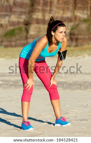 Exhausted fitness woman taking a break after running on summer at the beach.  Tired female runner resting. - stock photo
