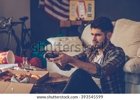 Exhausted gamer. Frustrated young man holding joystick while sitting on the floor in messy room after party - stock photo