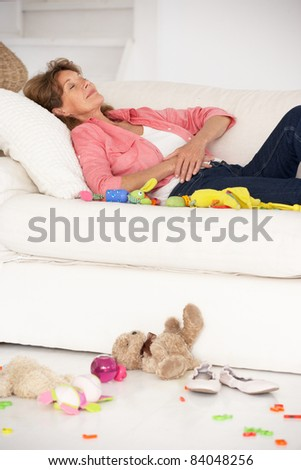 Exhausted grandmother enjoying a rest - stock photo