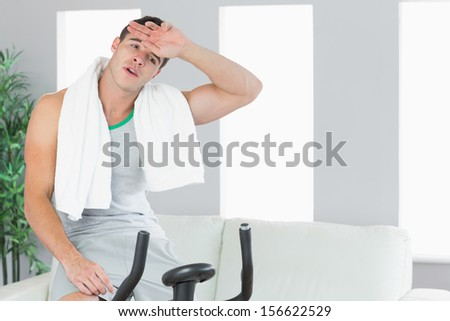 Exhausted handsome man exercising on exercise bike in bright living room - stock photo