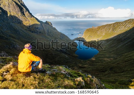Exhausted hiker relaxes and enjoys amazing view on rugged Lofoten mountains and coastline - stock photo