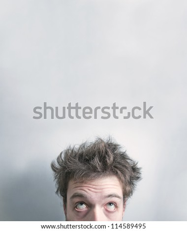 Exhausted man head over gray background with copyspace for your text. - stock photo