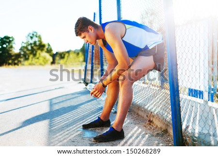 Exhausted man runner resting - stock photo