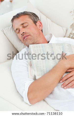 Exhausted man sleeping on the couch at home - stock photo