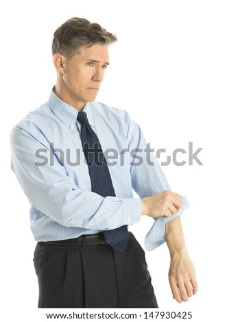 Exhausted mature businessman rolling up his sleeves while standing isolated over white background - stock photo
