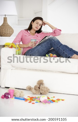 Exhausted mother enjoying a rest - stock photo