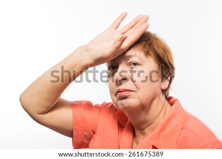 Exhausted old senior woman holding hand to her forehead