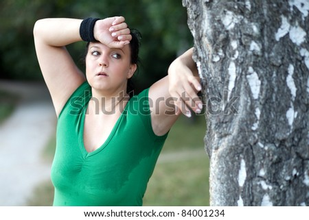 Exhausted overweight woman after a long run in the woods - stock photo