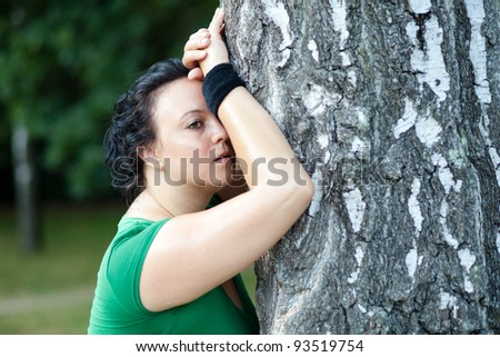 Exhausted overweight woman leaning on the tree and catching her breath after she finished her training - stock photo