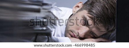 Exhausted overworked businessman lying with his head on desk at his office, panorama