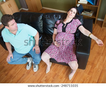 Exhausted pregnant female sitting on couch together - stock photo