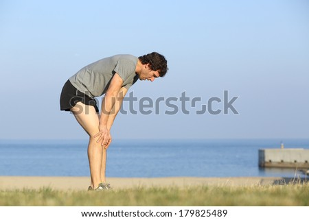 Exhausted runner man resting on the beach after workout with the ocean in the background               - stock photo