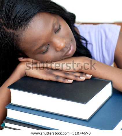 Exhausted student leaning on a stack of books against a white background - stock photo