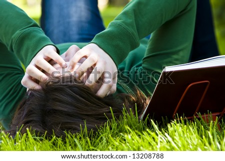 Exhausted student over the grass in the park - stock photo