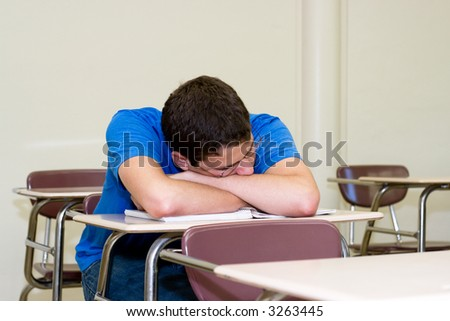 exhausted student takes a power nap in an empty classroom between final exams - stock photo