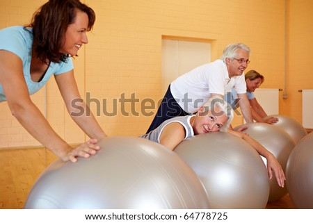 Exhausted woman in fitness class laying on exercise ball - stock photo