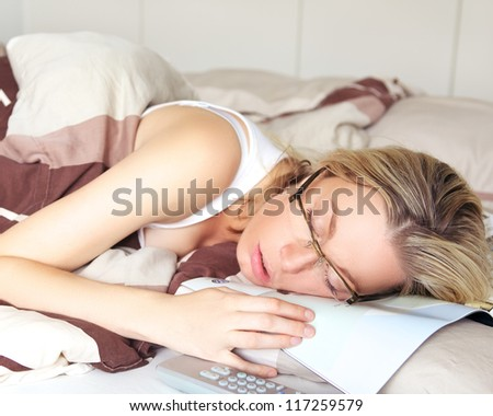 Exhausted woman sleeping in her glasses collapsed on top of the document she was reading - stock photo