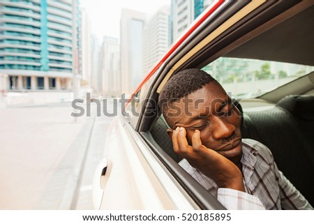 exhausted young african man sleeping in taxi