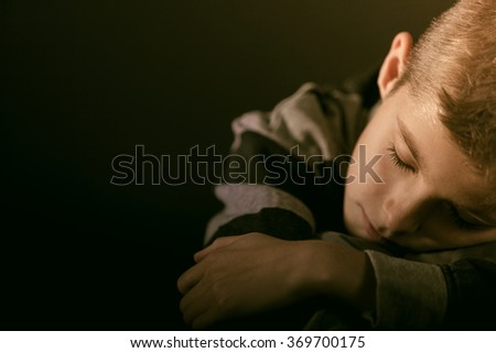 Exhausted young boy sleeping with his head on his arms resting on a table, close up view of his face in darkness with copy space