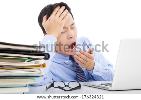 Exhausted young businessman yawning and holding his head - stock photo