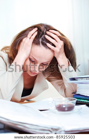 Exhausted young businesswoman reading documents