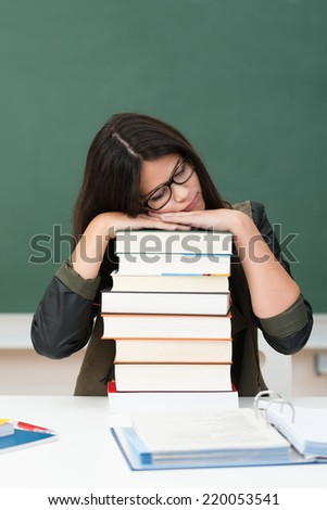 Exhausted young female student sleeping at her desk in class resting her head on a high stack of textbooks - stock photo