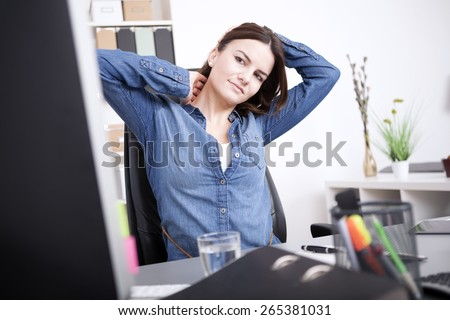 Exhausted Young Office Woman Sitting at her Office, Holding her Head and Neck While Looking at Computer Screen. - stock photo