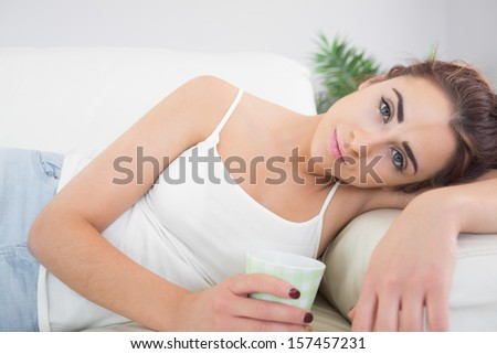 Exhausted young woman lying on a couch holding a cup