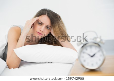 Exhausted young woman lying under the cover on her bed looking seriously at camera - stock photo