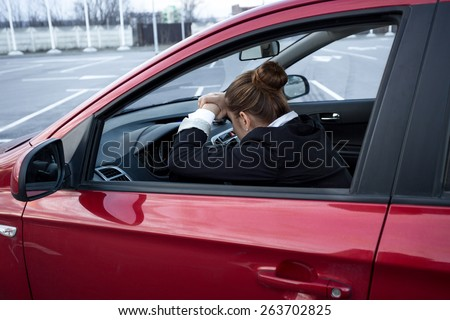 Exhausted young woman sleeping while driving a car - stock photo