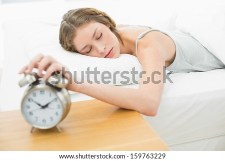 Exhausted young woman turning off the alarm clock lying in her bed - stock photo