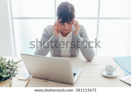 Exhausted young woman working at office desk touching her temples, she is having a bad headache, stressful life and illness concept - stock photo