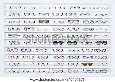 exhibitor of glasses consisting of shelves of fashionable glasses shown on a wall at the optical shop  - stock photo