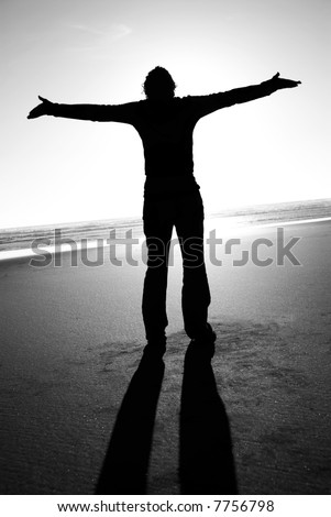 Exhilaration- a young woman with her arms spread looks to the sky - stock photo