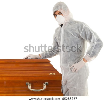 exhumation - man in protective workwear and mask with coffin - stock photo